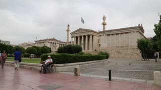 GREECE, ATHENS, JUNE 7, 2013: Destitute disabled person on invalid chair and people on the street near National Assembly building, Academy of Athens
