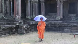 CAMBODIA, SIEM REAP, APRIL 3, 2014: Buddhist monk in orange clothes with blue umbrella in Angkor Thom - Khmer temple complex near Siem Reap city in Cambodia