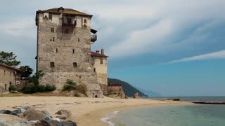 Old tower at the beach in Ouranoupoli, Athos peninsula, Chalkidiki, Greece. Ouranoupoli, formerly Ouranopolis,