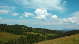 Time lapse of clouds and beautiful green mountains with coniferous trees. Video without birds and defects