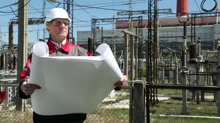 Station technical director with working drawings at nuclear power station. Worker in white helmet with engineering drawing near outdoor switchgear at nuclear power station