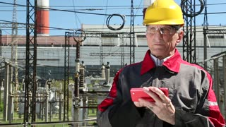 Power engineering specialist with red smartphone at heat electric power station. Worker in yellow hard hat at heat electric power station. Engineering supervision. Factory worker with red smartphone