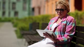 Senior woman sits on the bench and uses tablet computer. Woman with tablet computer