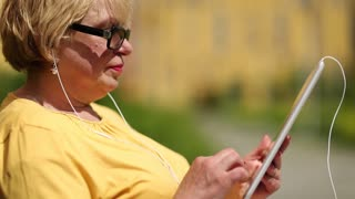 Senior woman in yellow jacket using tablet computer. Woman holding pad with headset