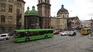 UKRAINE, LVIV, APRIL 5, 2015: Road traffic near the Dormition or Assumption church in old town of Lviv, Western Ukraine. The Church of the Assumption of the Blessed Virgin Mary