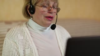 Woman with headphones with microphone talks to a customer via computer. Woman communicates using laptop
