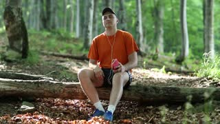 Adult man with red smartphone sits on a fallen tree in the forest and listens to music