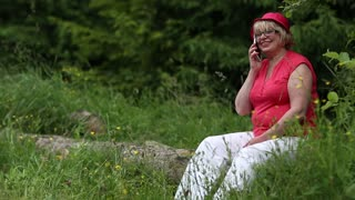 Woman in red cap sits on a fallen tree in the forest and communicates via smartphone