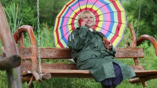 Senior woman with brightly coloured umbrella sits on the swing bench and communicates via cell phone