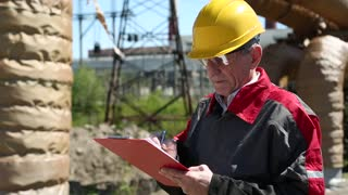 Construction engineer looks after building, wearing red and grey jacket and yellow helmet, writing down data in notebook