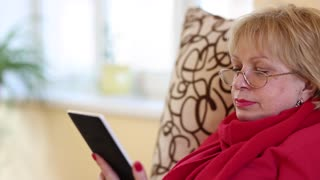 Blonde woman sitting on a couch and reading e-book. Woman with electronic book