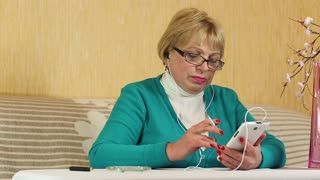 Senior woman in glasses with white smartphone sits at a table and smoking a cigarette
