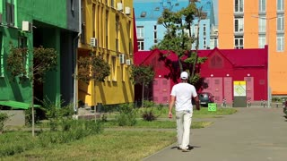 Man in white clothes walks down the street with many-coloured buildings
