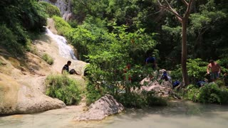 THAILAND, KANCHANABURI PROVINCE, APRIL 5, 2014: People at seventh level of seven-tiered Erawan Waterfall in Erawan National Park, Thailand