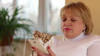 Senior blonde woman with white smartphone sits on the couch and listens to music