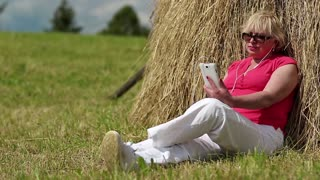 Senior woman in red t-shirt with white smartphone listening to music. Blonde woman with white smartphone sitting near haystack and listening to music
