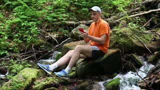 Adult man with red smartphone sits on a stone near small river and listens to music