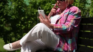 Senior woman with cigarette sits on the bench and communicates via smartphone