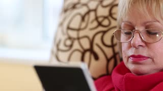 A senior woman sits on a sofa and uses electronic book. A woman reading a book
