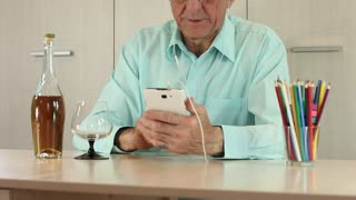 Senior man with white mobile phone and bottle of cognac sits at a table. Man in blue shirt with white smartphone sits at a table