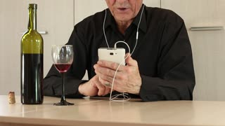 Man with white cell phone sits at a table in office and drinks wine. Senior man in black shirt sits at a table, drinks wine and communicates via smartphone. Grey-haired senior man pours wine in glass