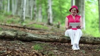 Senior woman in red hat sits on a fallen tree in deciduous forest and communicates via tablet PC