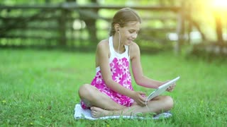 Beautiful girl in pink dress with tablet computer sits on the grass in garden at sunset. Girl communicates via tablet computer. Little girl with tablet PC sits on the grass in the garden
