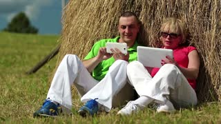 Man with white smartphone and woman with white tablet PC sits near a haystack. Mother and son with tablet computer and smartphone looks and flips through the photos in their devices