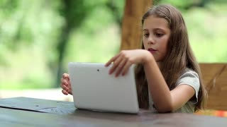 Beautiful girl with white tablet computer sits on the bench in summerhouse. Girl playing the game on his Tablet PC. Little girl with tablet computer sits on the bench in bower