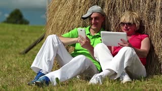 Mother and son in green t-shirts with tablet computer and smartphone looks and flips through the photos in their devices. Man with white smartphone and woman with white Tablet-PC sits near haystack