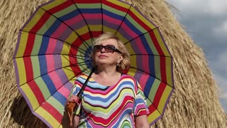 Blonde woman in glasses with brightly coloured umbrella stands near haystack and looks into the distance. Senior woman with many-coloured umbrella stays near hayrick