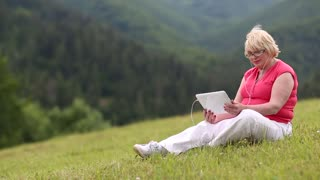 Pretty woman sits in the meadow on green grass and communicates via tablet computer. Woman sitting in meadow talks on skype, gestures and smiles. She has blond hair, red t-shirt and glasses