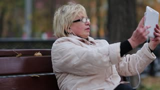 Blonde woman sits on the bench near the road and makes photos on his tablet computer. Senior woman in glasses sits on the bench and records videos on his white Tablet-PC