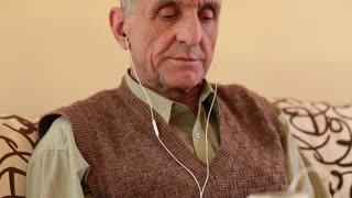 Senior man with white smartphone sits on the couch and listens to music. Music lover
