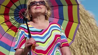 Blonde woman in sun glasses with many-coloured umbrella stands near haystack and looks into the distance. Senior woman with many-coloured umbrella stands near hayrick. Female with umbrella