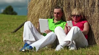 Man with tablet computer and woman with smartphone sits near a haystack. Mother and son with tablet computer and smartphone looks and flips through the photos in their devices. Male and female, couple
