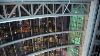 View from glass elevator at night, Dubai, United Arab Emirates. Lift rises. Dubai is a city and emirate in the UAE. The emirate is located south of the Persian Gulf on the Arabian Peninsula