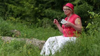 Blonde woman in red cap sits on fallen tree in the forest listens to music and waving hands. Female with white smartphone. Businesswoman with mobile phone in the wood. Cheerful woman listens to music