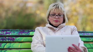 Blonde woman sits on the bench in public garden and uses white tablet computer. Female with tablet computer. Business woman with Tablet PC