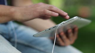 Man holds in hands white tablet pc. Man looks the photos in his tablet computer. Closeup of man hands with white tablet pc and earphones. Man looks and flips through the photos in his computer
