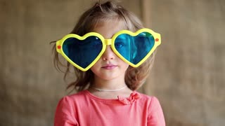 Funny little girl in yellow and blue glasses looks at the camera and shows tongue. Little girl in big sunglasses in the shape of hearts looks at the camera