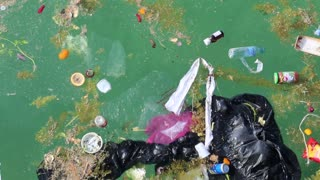 Abuse of environment. Garbage floats in the sea. Muddy water