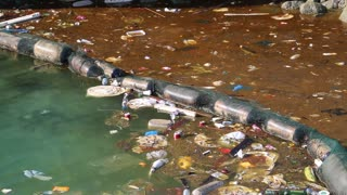 Abuse of environment. Muddy water. Garbage floats in the sea near the coast