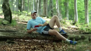 Adult man in blue t-shirt with red smartphone lies on a fallen tree in the forest. Man with smartphone and earphones