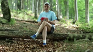 Adult man in blue t-shirt with red smartphone sits on a fallen tree in the forest. Man with smartphone and earphones
