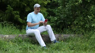Adult man in blue t-shirt with red smartphone sits on a fallen tree in the forest. Man with smartphone. Boy sits on a fallen tree and uses his cell phone