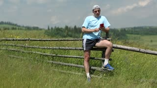 Adult man in blue t-shirt with red smartphone stands in the field and listens to music. Man listens to the radio