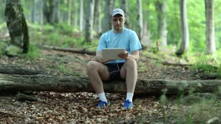 Adult man in blue t-shirt with Tablet PC sits on a fallen tree in the forest. Man records videos on his tablet computer