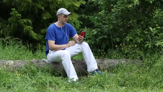 Adult man in dark blue t-shirt with red smartphone sits on a fallen tree in the forest. Man with smartphone. Boy sits on a fallen tree and uses his mobile phone