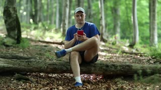 Adult man in dark blue t-shirt with red smartphone sits on a fallen tree in the forest